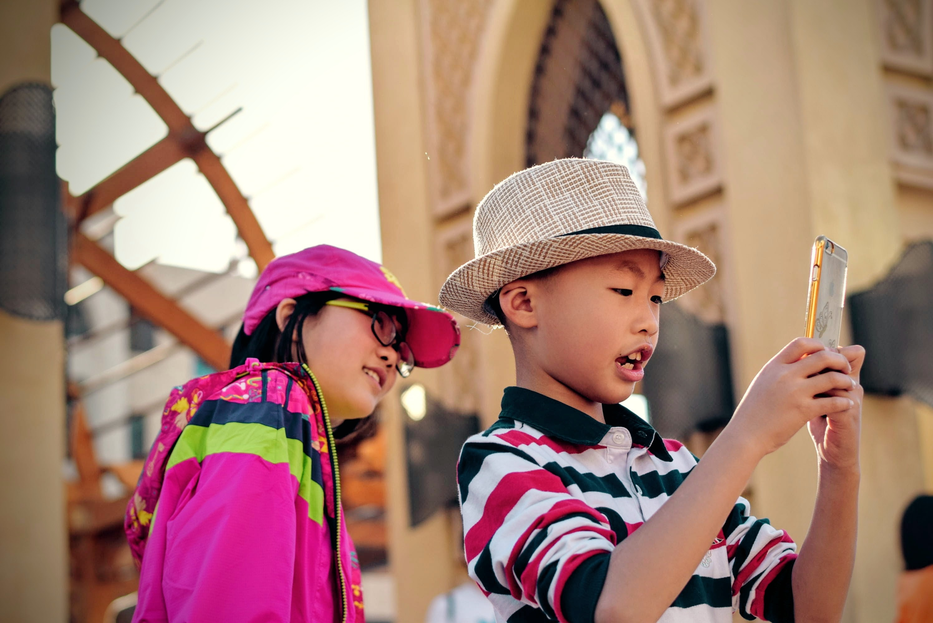 A photo of two children taking selfies on a smartphone